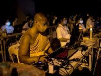 A Buddhist monk manages a video conferencing for people unable to attend Makha Bucha celebrations due to the Covid-19 coronavirus pandemic at Wat Dhammakaya, north of Bangkok on February 26, 2021. Jack TAYLOR / AFP