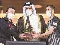 Sheikh Joaan bin Hamad al-Thani presents the Qatar Cup trophy to Al Sadd captain Hassan al-Haydos (right) and coach Xavi Hernandez (left). (Photo: Noushad Thekkayil)