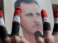 Two men, with the fingers painted in the colours of the Syrian flag, show the V-sign as they pose in front of a huge image of President Bashar al-Assad