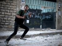 Syrian rebel aims his weapon during clashes with government forces