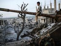 Syrian Kurdish boy sits on a destroyed tank in the Syrian town of Kobane