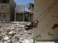 Syrian boy plays on a swing in a destroyed building
