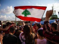 Protesters raise the Lebanese Flag