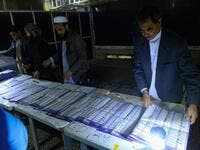 In this photo taken on October 20, 2018, Afghan Independent Election Commission (IEC) officials count ballot papers at a polling centre for the country's legislative election in Herat province. 