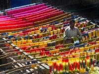 A Pakistani worker dries fabric threads after dyeing them at a factory in Lahore 