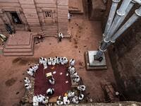 Ethiopian Orthodox devotees gather near the pillar of a shelter that protects the rock-hewn structure from erosion of the church of Saint Emmanuel in Lalibela, Ethiopia 