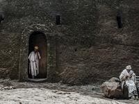 An Ethiopian Orthodox priest steps out of a room of the rock-hewn church of the House of the Saviour of the World in Lalibela, Ethiopia 