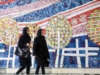 To women walks along a street past a mosaic mural on the first anniversary of the nuclear agreement in Tehran (Twitter)