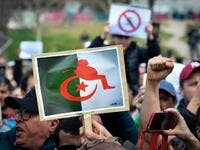 Protesters hold placards during a sit-in against the Algerian presidential bid for a fifth term in office