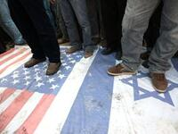 Islamic Jihad supporters walk at the USA and Israeli flag during a demonstration to mark the second anniversary of Israel's three-week offensive on the Gaza Strip.