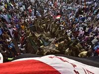Sudanese demonstrators surround soldiers as they gather near the military headquarters in the capital Khartoum  (AFP)