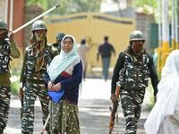 Indian paramilitary troopers patrol as a Kashmiri woman voter looks on in Srinagar  (AFP)