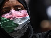 A masked Sudanese protester rallies outside the army complex in Sudan's capital Khartoum (AFP)