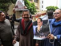 Egyptians pose for a picture with a newspaper front page and a poster of President Abdel Fattah al-Sisi (AFP)