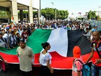 Protesters chant slogans and wave a giant Palestinian flag as they march in a demonstration in the Moroccan capital Rabat  (AFP)
