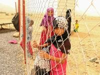 A displaced Yemeni girl looks on from a wire fence at a make-shift camp in the country's northern Hajjah province  (AFP)