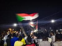 Sudanese demonstrators wave national flags as they protest in the streets of the capital Khartoum to demand civilian rule  (AFP)