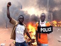 Protesters pose with a police shield outside the parliament in Ouagadougou on October 30, 2014 /AFP