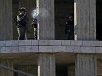 An Israeli soldier fires a tear gas canister at Palestinian stone throwers following a raid in the West Bank city of Ramallah. (AFP)