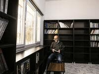 Ziad al-Hamad, director of the first cultural centre to open since ISIS rule ended in the eastern Syrian city of Raqa. He holds a book as he sits in its library on May 1, 2019. Delil souleiman / AFP
