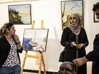 Residents of the eastern Syrian city of Raqa view artworks during an exhibition at the first cultural centre to open since ISIS rule ended there, on May 1, 2019. DELIL SOULEIMAN / AFP