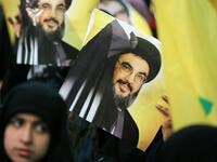 A Shiite supporter holds a poster showing Hassan Nasrallah, the head of Lebanon's militant Shiite Muslim movement Hezbollah. (AFP/ File)