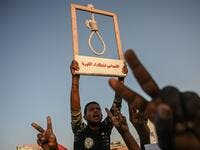 A Sudanese protester holds a hanging rope as others flash victory sign during a protest outside the army headquarters in the capital Khartoum on April 21, 2019. (AFP/ File)