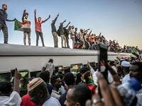 Sudanese protesters from the city of Atbara, flash the V-sign for victory and wave national flags atop a train, as it arrives at the Bahari station in Khartoum on April 23, 2019. (AFP/ File Photo)