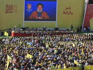 Hasan Nasrallah, the head of Lebanon's militant Shiite movement Hezbollah, delivers a speech on a screen during a commemoration marking the 13th anniversary of the end of the 2006 war with Israel in the southern Lebanese town of Bint Jbeil on August 16, 2019. (AFP)