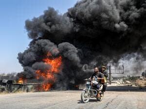 Men ride a motorcycle past a plume of smoke from a blaze at a vehicle gathering point for civilians fleeing from the south of Idlib province, which was hit by reported government forces' bombardment (AFP)