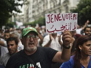 "An Algerian protester holds a placard reading ""I won't vote"", during a demonstration against the ruling class in the capital Algiers on September 13, 2019, for the 30th consecutive Friday since the movement began. (AFP/ File Photo)"