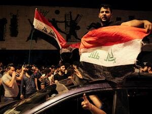 Iraqi protestors wave Iraq's national flags frome a car;s sun-roof as they take part in anti-government demonstrations in Baghdad's Tahrir Square on October 24, 2019. Anti-government rallies renewed across Iraq late on October 24, 2019, the second phase of protests denouncing corruption and unemployment before evolving into calls for an overhaul of the political system that turned deadly earlier this month and which could balloon after the endorsement of populist cleric Moqtada al-Sadr. AFP