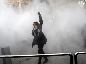 An Iranian woman raises her fist amid the smoke of tear gas at the University of Tehran during a protest driven by anger over economic problems, in the capital Tehran. (AFP/ File Photo)
