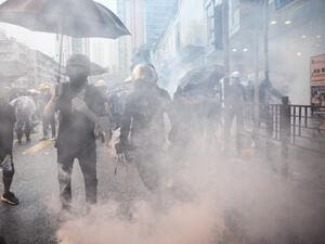 In this picture taken on August 25, 2019, Abby (centre R), 19, and her boyfriend Nick (centre L, holding tongs), 20, react after police fired tear gas during a protest in Tsuen Wan, an area in the New Territories in Hong Kong. ANTHONY WALLACE / AFP