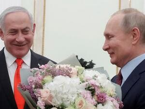 Russian President Vladimir Putin holds flowers next to Israeli Prime Minister Benjamin Netanyahu as they meet at the Kremlin in Moscow on January 30, 2020. MAXIM SHEMETOV / POOL / AFP