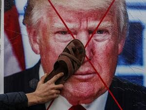 A Palestinian protester sticks his footwear on a poster depicting the face of US President Donald Trump during a demonstration against Trump's Middle East peace proposal in Khan Yunis in the southern Gaza Strip on February 3, 2020. SAID KHATIB / AFP