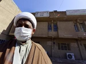 A cleric wearing a protective mask stands outside the building of a religious school which attracts predominantly foreign students and where the first Iraqi case of novel coronavirus infection was confirmed, during its disinfection in the central Iraqi shrine city of Najaf, on March 9, 2020. Haidar HAMDANI / AFP
