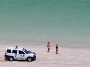 Bathers stare at a police car patroling a public beach at the Jumeirah Beach Residence in the Gulf city of Dubai on May 25, 2020. GIUSEPPE CACACE / AFP