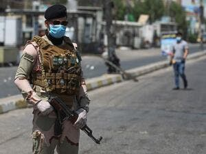 A member of the Iraqi security forces stands guard at a checkpoint, enforcing a curfew due to the COVID-19 coronavirus pandemic, in Baghdad's eastern Sadr City suburb on May 31, 2020. The Iraqi authorities imposed a week-long curfew to curb the latest increase in infections of coronavirus in the country. AHMAD AL-RUBAYE / AFP