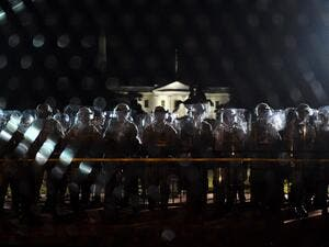 Police officers hold a perimeter behind the metal fence recently erected in front of the White House demonstrators gather to protest the killing of George Floyd on June 2, 2020 in Washington, DC. Anti-racism protests have put several US cities under curfew to suppress rioting, following the death of George Floyd in police custody. Olivier DOULIERY / AFP