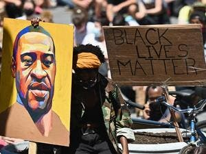 "Protesters hold up signs during a ""Black Lives Matter"" protest in front of Borough Hall on June 8, 2020 in New York City. On May 25, 2020, Floyd, a 46-year-old black man suspected of passing a counterfeit $20 bill, died in Minneapolis after Derek Chauvin, a white police officer, pressed his knee to Floyd's neck for almost nine minutes.  Angela Weiss / AFP"