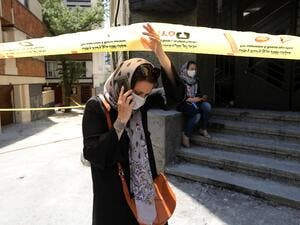 A mask-clad Iranian woman walks past the security cordon at the site of an explosion at the Sina At'har health centre in the upmarket northern neighbourhood of Tajrish in the capital Tehran on July 1, 2020. Iranian police questioned four people as part of investigations into a powerful explosion that killed 19 people at a Tehran clinic the night before, state media reported. ATTA KENARE / AFP