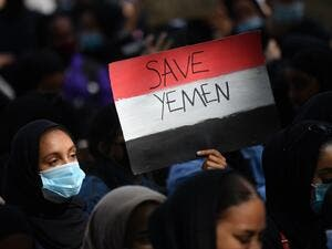 A protester holds a Yemeni flag-themed placard in Parliament Square in London on July 5, 2020, as she demonstrates against the continued conflict in Yemen. Yemen has been locked in conflict since the Huthis took control of Sanaa in 2014 and went on to seize much of the north. The crisis escalated when the Saudi-led coalition intervened the following year to support Yemen's internationally-recognised government. Tens of thousands of people, mostly civilians, have been killed and millions displaced in what th