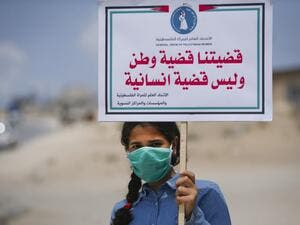 "A Palestinian girl wearing a protective mask amid the COVID-19 pandemic lifts a placard which reads ""Our cause that of a homeland, not a humanitarian one"", during a rally for supporters of the Fateh movement against Israel's West Bank annexation plans, in Beit Hanun in the north of the Gaza Strip, on July 6, 2020. Mohammed ABED / AFP"