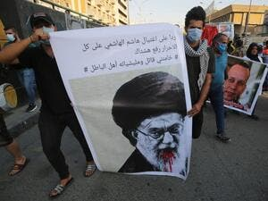 "Iraqi demonstrators attend a symbolic funeral for slain Iraqi jihadism expert Hisham al-Hashemi, who was shot dead yesterday outside his house in the Iraqi capital, on July 7, 2020 at Baghdad's Tahrir square. Slogan reads in Arabic: ""in response to the killing of Hashem al Hashemi, all free are to use the hashtag ""Khamenei (Iran's Supreme Leader Ayatollah Ali Khamenei) is a killer and his militias are wrongdoers"". (AHMAD AL-RUBAYE / AFP)"