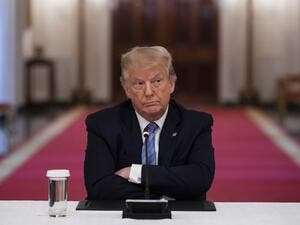 US President Donald Trump sits with his arms crossed during a roundtable discussion on the Safe Reopening of America's Schools during the coronavirus pandemic, in the East Room of the White House on July 7, 2020, in Washington, DC. JIM WATSON / AFP
