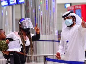 A tourist receives instruction at Dubai airport in the United Arab Emirates on July 8, 2020, as the country reopened its doors to international visitors in the hope of reviving its tourism industry after a nearly four-month closure. GIUSEPPE CACACE / AFP