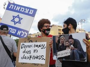 Israelis lift placards during a demonstration in Rabin Square in the central coastal city of Tel Aviv, on July 11, 2020, to protest the government's abandonment of the country's self-employed and other sectors after forcing their businesses to close under COVID-19 regulations, according to the organizers. Jack GUEZ / AFP