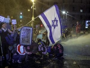 Protesters crouch down as police use water cannons as they clash during demonstrations against the Israeli government near the Prime Minister's residence in Jerusalem on July 25, 2020. AHMAD GHARABLI / AFP