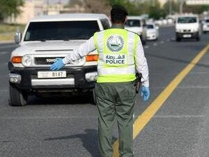 A policeman stops vehicles at a security checkpoint to examine passengers for exit permits in Dubai on April 9. (AFP)